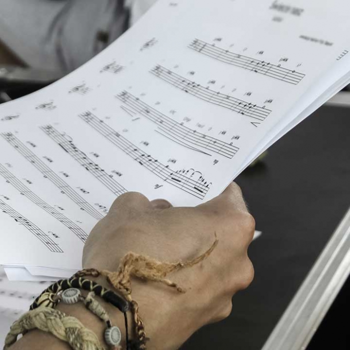 Person holding music sheets.